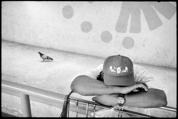 Man takes a break from shopping while bird looks on.